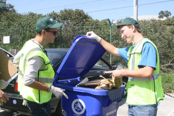Mira Costa juniors Joe Rosenberg, left, and Ben Manclark, right, discuss the contents of a recycling bin in El Porto. Photo by Kelley Kim