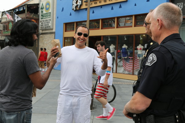 Hermosa Beach Police Captain Tom Thompson and Fire Chief David Lantzer advise two German tourists that unlike Munich during Octoberfest, drinking in public is not allowed in Hermosa Beach.