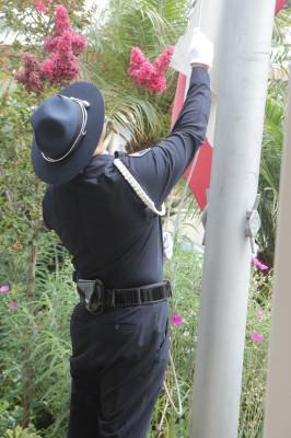 Hermosa Beach Police Detective Jonathan Cruz raises the flag following the ceremony.