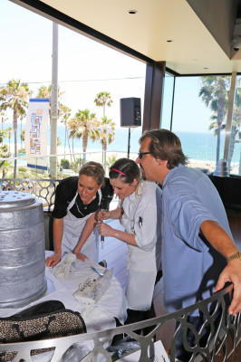 Shade Hotel sous chef Ashley Oates touches up the Stanley Cup cake while an assistant and Michael Zislis look on.