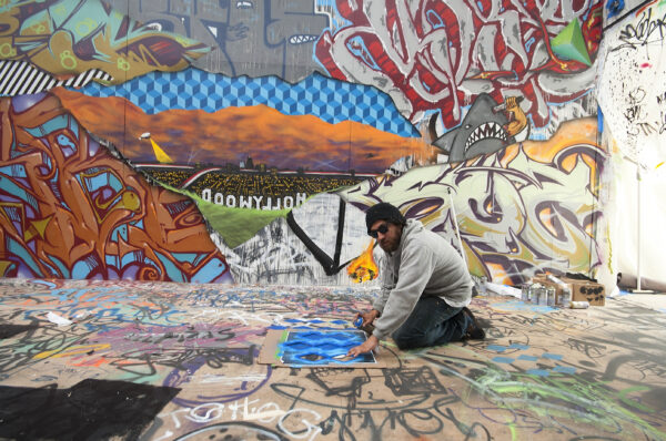 Graffiti artist Fishe with his work at ESMoA. Photo by Gloria Plascencia, contributing photographer