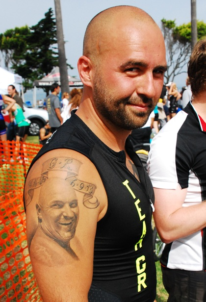 Andrew Giardino proudly displays the tattoo of his father Michael, who died last year after finishing the swim at the Redondo Beach Triathlon. Photo by Randy Angel