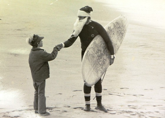 """""""Surfing Santa"""" (Paul Matthies) is interviewed by the """"Littlest Reporter"""" (Loyal Pennings) for an Easy Reader story in 1978. Photo by Kevin Cody"""