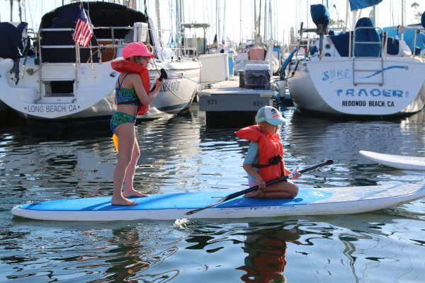 Bella, 8, and Emma, 6, tandem paddle in King Harbor.