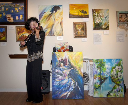 Artist - and violinist - Julliena Okah, with her work at 608 North in Redondo Beach. GLORIA PLASCENCIA, CONTRIBUTING PHOTOGRAPHER
