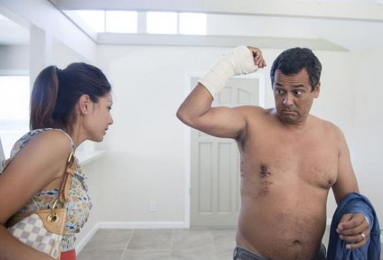 Lynn Kim of Rancho Palos Verdes visits her friend and co-worker Steve Robles, 50, of Lomita who shows her his stitches from a great white shark attack he suffered Saturday morning in Manhattan Beach. Photo by Cindy Yamanaka