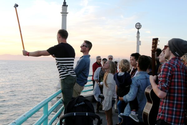 Slater Trout sets up a selfie with fellow Instagramers at the end of the Manhattan Beach pier.
