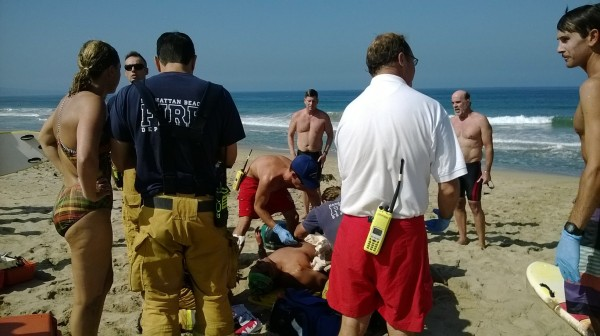 "Los Angeles County Lifeguard Captain Stacy Lizotte oversees fellow lifeguards and Manhattan Beach paramedics treat shark bite victim Steve Robles. Photo by John ""Biff"" Collins"