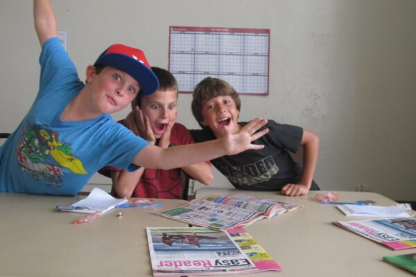 Jamison Perrault, Jacob Less and Josh Beste react to the local news in Easy Reader at last year's camp. Photo by Kevin Cody, staff.