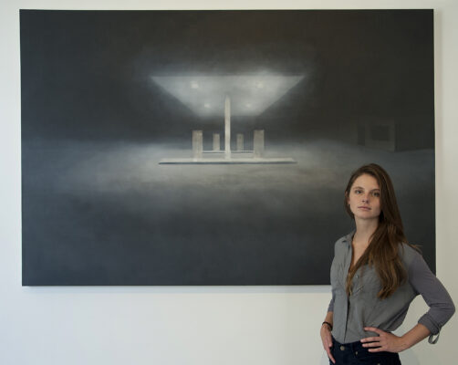 Natalie Arnoldi with one of her gas station paintings GLORIA PLASCENCIA, CONTRIBUTING PHOTOGRAPHER