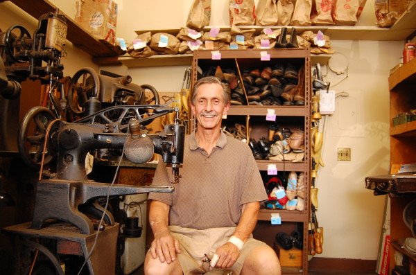 """Bill Cotter owns and operates Manhattan Shoe Repair at 1010 Manhattan Ave. with his wife Kathy. The downtown shop, founded by his grandfather John, recently celebrated its 80th anniversary. His advice on how to run a successful independent business? """"Have something people want and deliver what you promise you'll deliver,"""" he says. Many of his clients have been returning to the shop for decades. Photo by Esther Kang"""