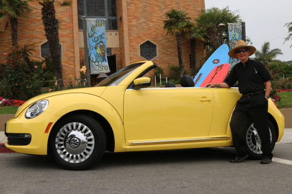 """""""I loved driving it, but it drew too much attention,"""" the famously reclusive Monsignor John Barry said of the yellow VW Beetle he is raffling off for the parish school. Photo by Kevin Cody"""