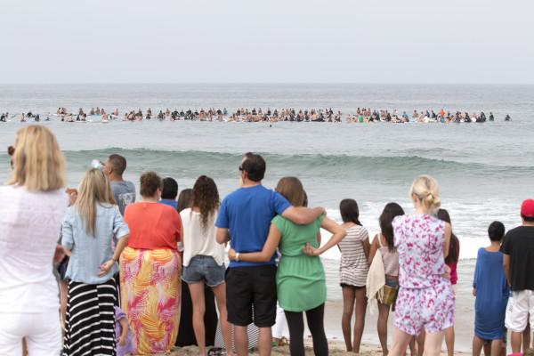Onlookers watch the paddle out Friday morning in memory of Clint Clausen, a Manhattan Beach restaurant owner. Photo by Brad Jacobson