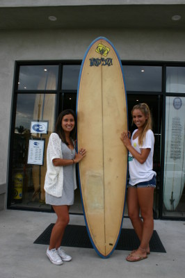 Dive N' Surf's Lani Kawashima and Riley Staal show one of the vintage longboards that will be exhibited at the Longboard Collector Club show on Saturday at Dive N' Surf. Photo by Eddie Solt