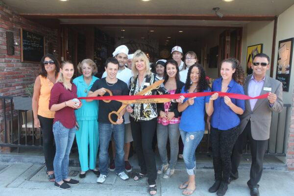 Hermosa Beach Chamber of Commerce CEO Maureen Hunt (center) with Creme de la Crepe owner Bruno Baio (holding scissors) during the restaurants reopening earlier this year.