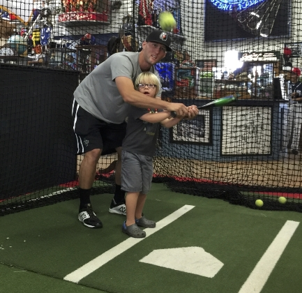 Five-year-old Ryder Shields gets batting tips from Nigel Nootbaar. Photos courtesy of Beach City Baseball Academy