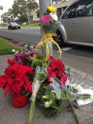 Flowers commemorating victims of the car accident, set at the corner of Vincent Street and Pacific Coast Highway in front of St. James Catholic Church.