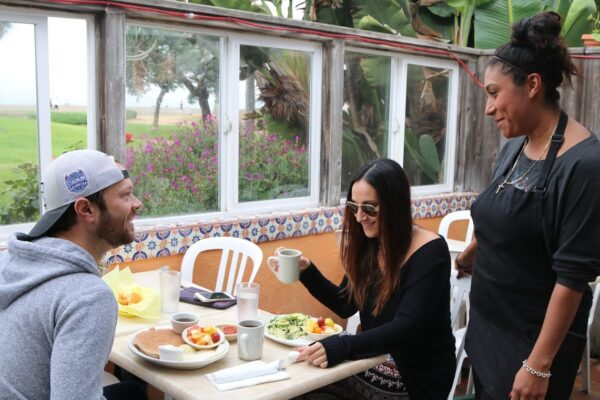 La Playita server Fatima Velazquez with Hermosa Beach regulars Zac Short and Erin Cutler in the restaurant's garden patio, which looks out on Noble Park and the ocean. Photo by Kevin Cody