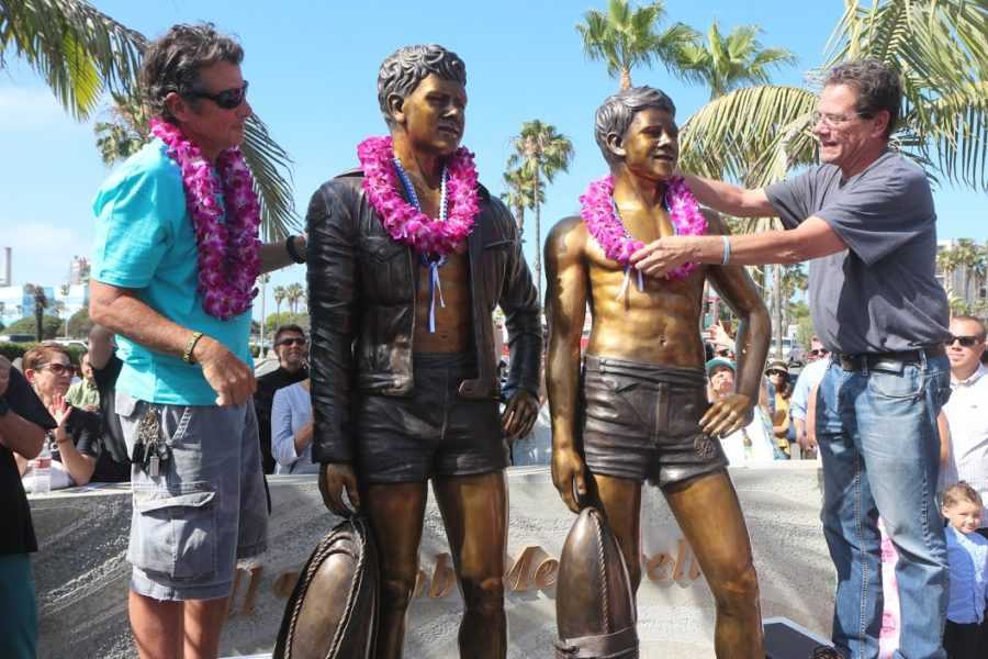 Perhaps the only uncontroversial improvement proposed for King Harbor in 2014 was the unveiling of the Bill and Bob Meistrell statues. Billy and Robbie Meistrell place leis on the statues of their twin parents, who were the founding owners of Dive N' Surf and Body Glove. Photo by Kevin Cody