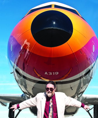 Food in the Air and Space author Richard Foss with an Airbus 319 painted with Pacific Southwest Airline colors. The San Diego-based, discount airline painted smiles on the nose of  all of its airplanes, which became known as PSA Grinningbirds. The airplane is on display at the Flight Path Museum near LAX. Photo by David Fairchild