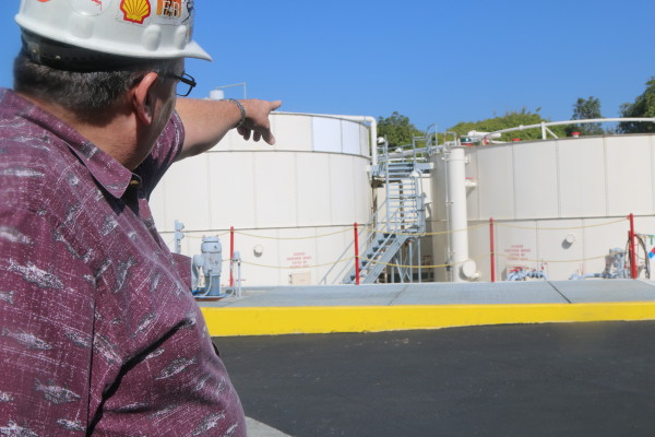 Louis Zylstra, head of E & B Natural Resources facilities in the Los Angeles area, points to the company's facility in Huntington Beach. Photo by Kevin Cody.