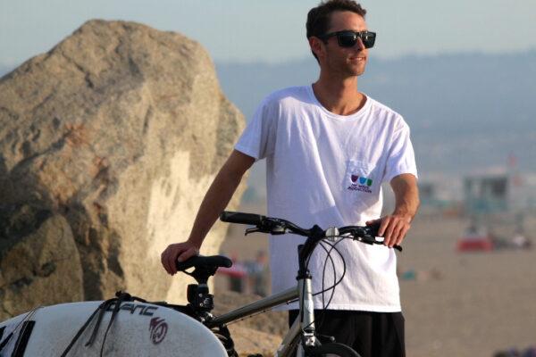 Cameron Brown biking to surf. Photo by Ryan Boyles