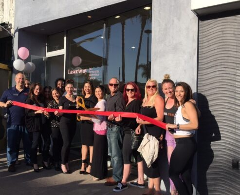 "Ribbon cutting LA LaserAway general manager Stacy Trujeque (with scissors) is joined by her staff and members of the Hermosa Chamber of Commerce on April 9 for a ribbon cutting of the chain's 20th location, at 1312 Hermosa Avenue. The chain gained prominence following a visit by Kim Kardashian, which was featured on ""Keeping up with the Kardashians."""