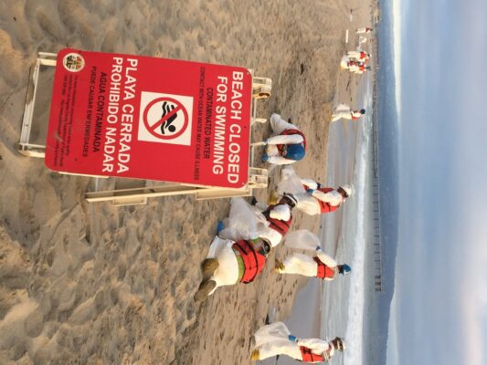 A cleanup crew picks up tar in Manhattan Beach. Photo by Betsy Ryan
