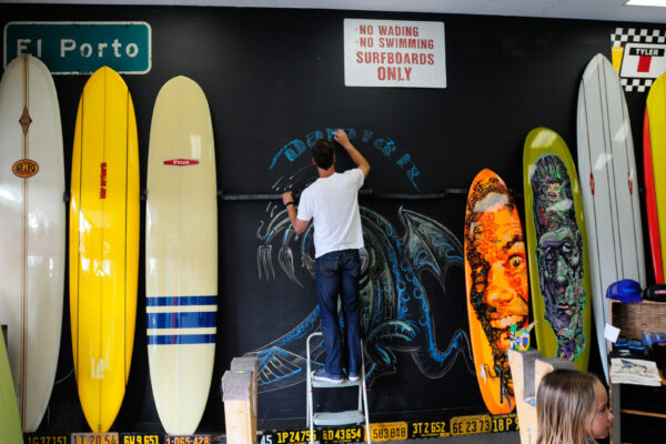 Damian Fulton creating a mural at Tyler Surfboards on Grand Avenue. Photo by Chris Miller.