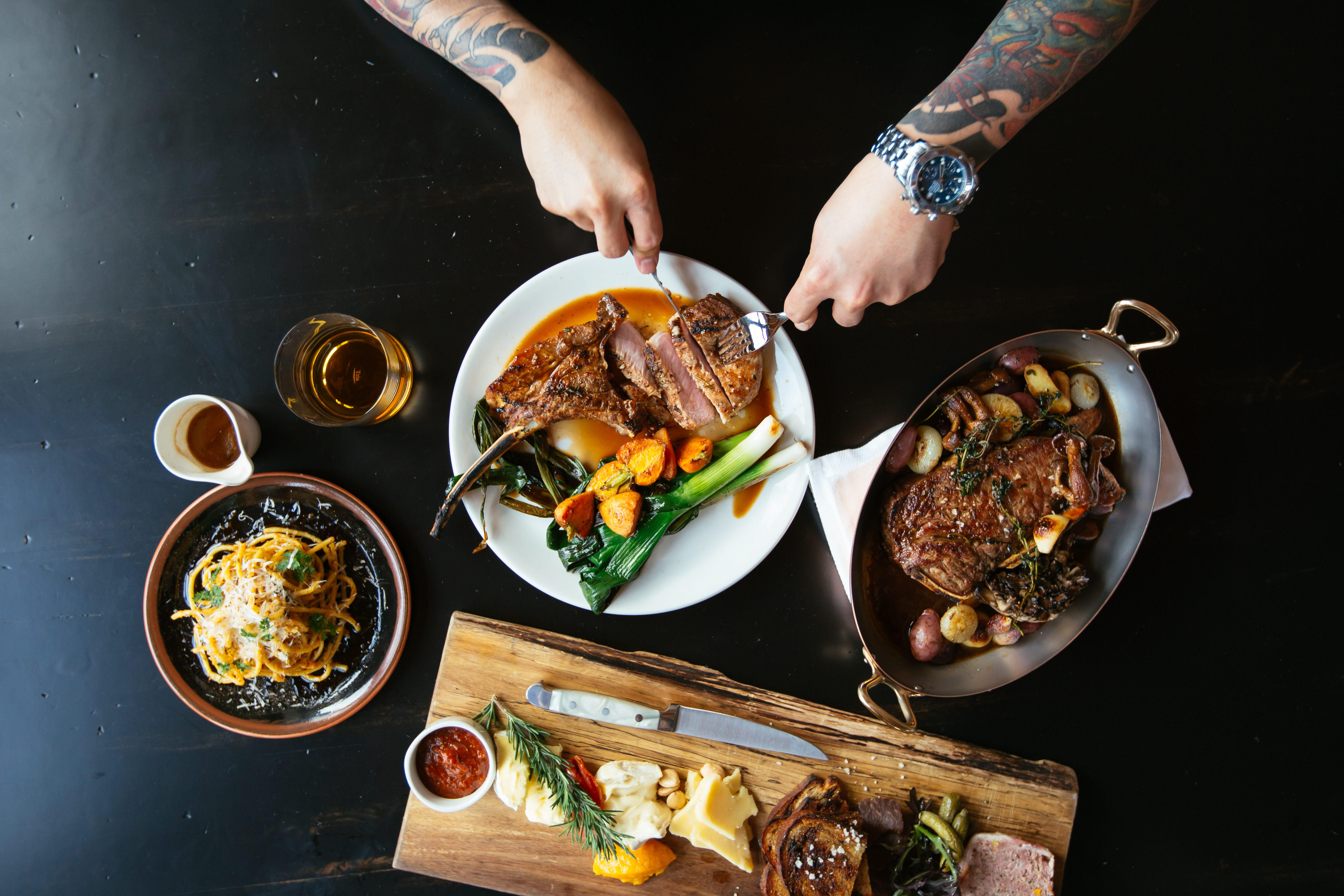 A Steak & Whisky spread (clockwise from left): bucatini; smoked duroc pork chop; rib eye; and a charcuterie/cheese board. Photo by Lanewood Studio