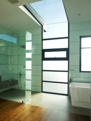 Natural light fills the bathroom through a floor to ceiling window that meets up with a skylight.