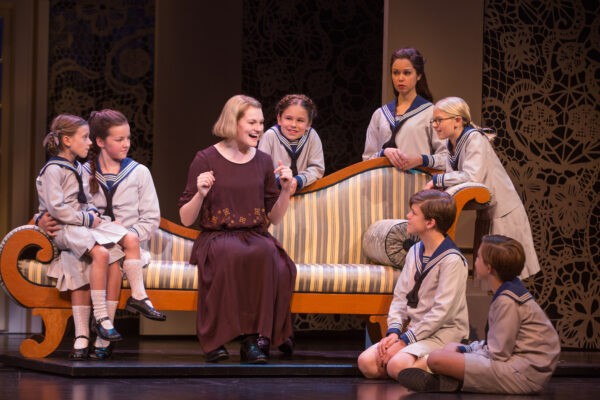 Kerstin Anderson as Maria Rainer, joined by the von Trapp children. Clockwise from left: Audrey Bennett as Gretl, Maria Knasel as Louisa, Mackenzie Currie as Marta, Paige Silvester as Liesl, Svea Johnson as Brigitta, Erich Schuett as Friedrich, and Quinn Erickson as Kurt. Photo by Matthew Murphy