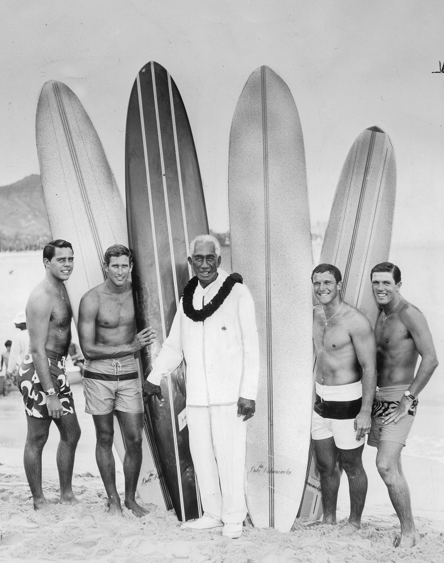 """Kahanamoku, center, stands with his all-star surfing team. From left to right: Paul Strauch Jr., inventor of the """"cheater five""""; Joey Cabell, founder of the Chart House restaurant chain; Fred Hemmings, 1968 world champion; and Butch Van Artsdalen, pioneer of Banzai Pipeline. Photo by Bob Johnson, Los Angeles Herald-Examiner."""