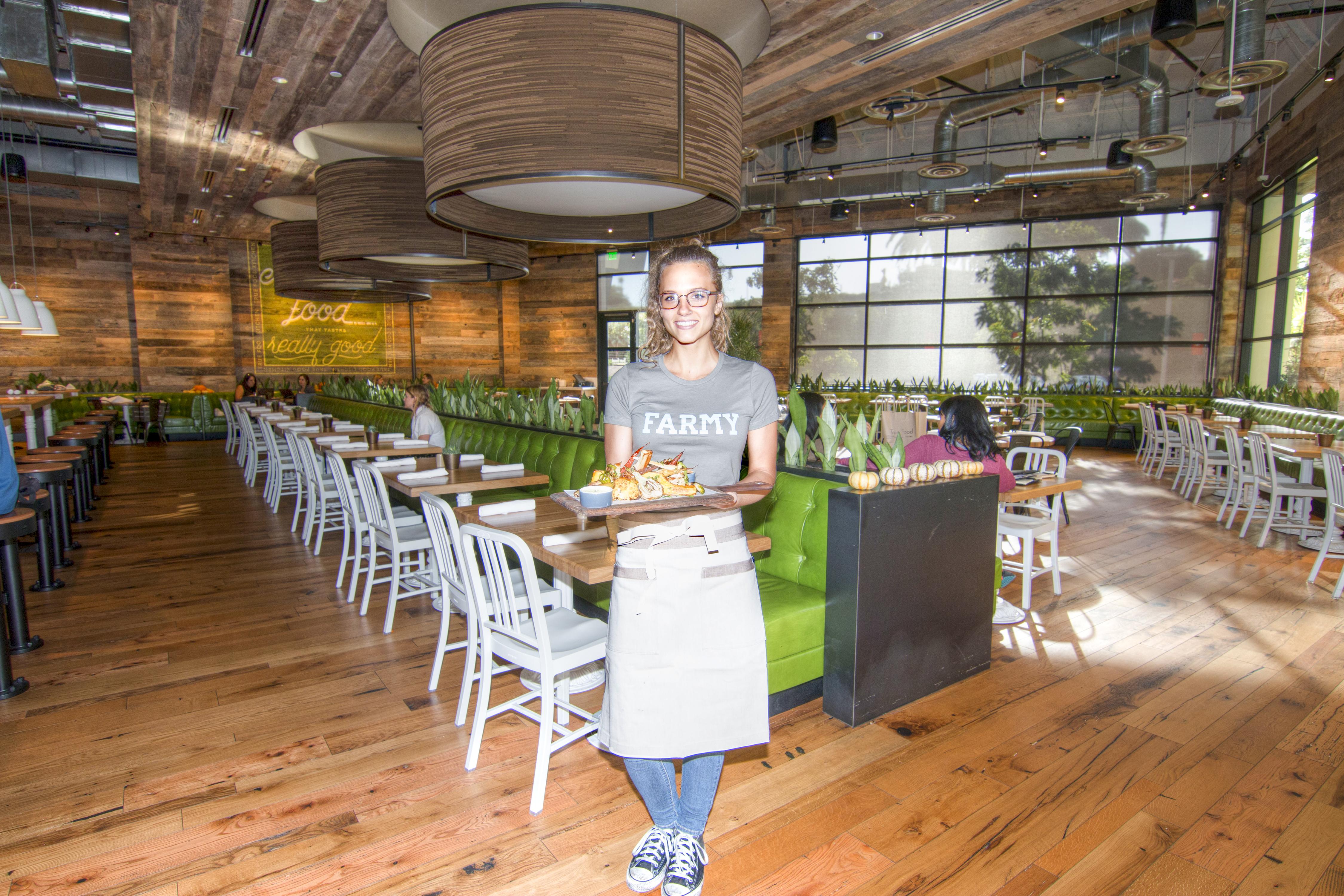 True Food Kitchen's Julia Cox serves the roasted seasonal vegetable board. Photo by Brad Jacobson