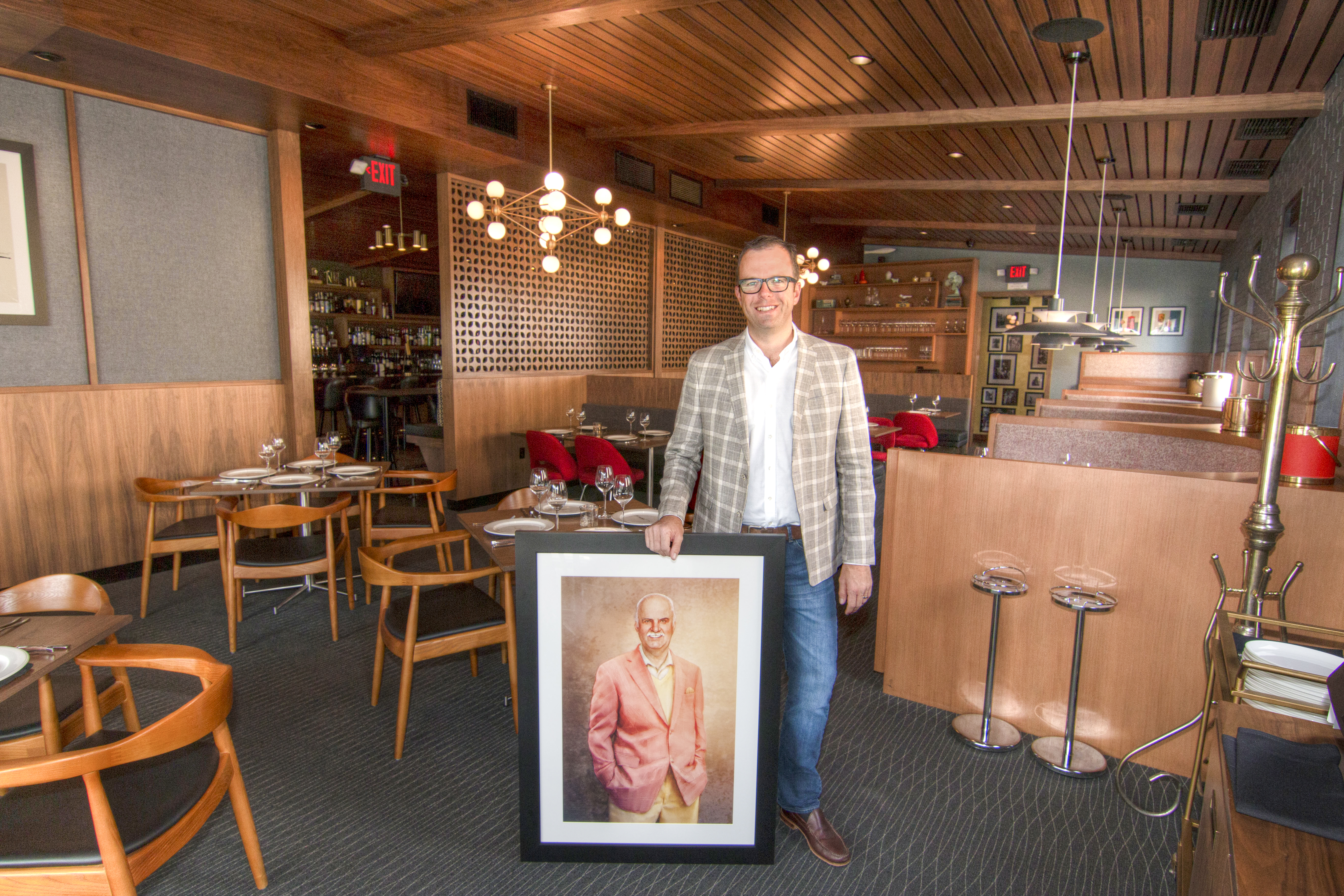 The Arthur J co-owner Mike Simms with a portrait of his grandfather Arthur J. Simms. Photo by Brad Jacobson