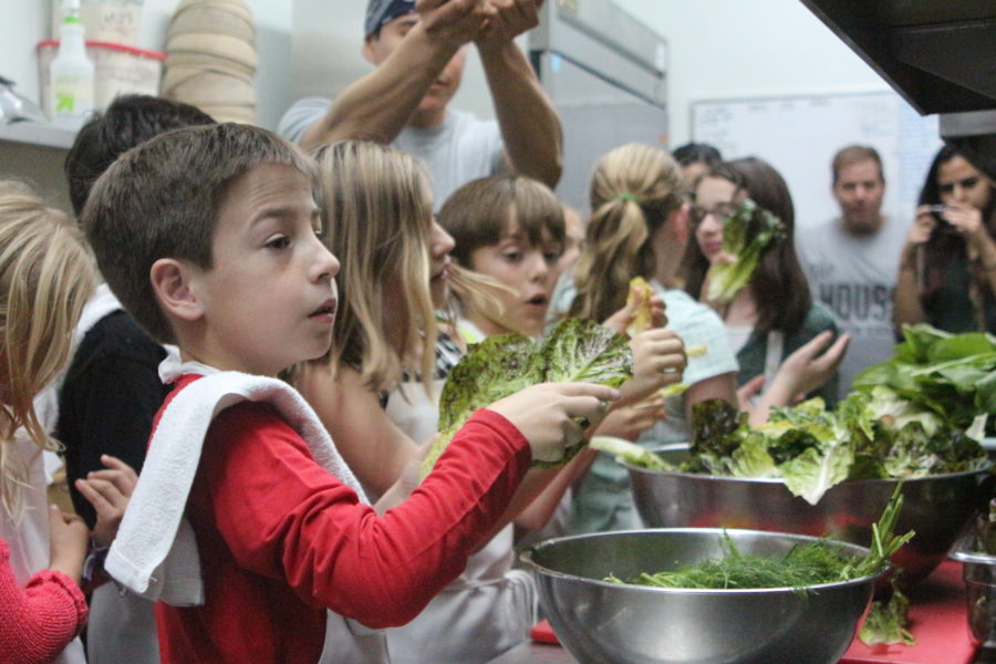 Pacific Elementary students break apart lettuce in the Manhattan House kitchen with Chef Mike. Photo by Caroline Anderson