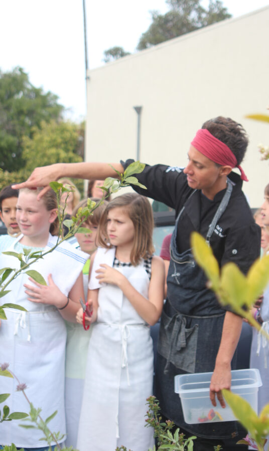 Manhattan House Chef Diana Stavaridis collecting edible flowers with students from Pacific Elementary School outside of the restaurant. Photo