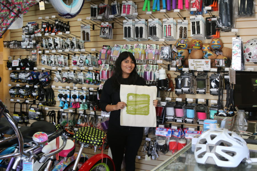 Employee Stephanie Villasenor holds one of the reusable bags deployed by Hermosa Cyclery. The store was one of several in the city to get a jump on the plastic bag ban. Photo by Ryan McDonald