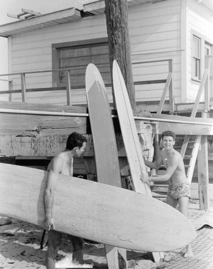 Jerry Cunningham at the Manhattan Beach pier holding the first balsa surfboard ever shaped by Greg Noll. The board is now in the Surfing Heritage Museum in San Clemente.