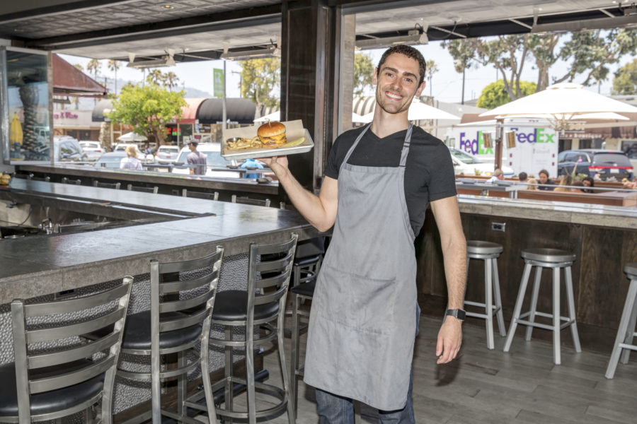 Rebel Republic's Matthew Konen with a Rebel burger. Photo by Brad Jacobson