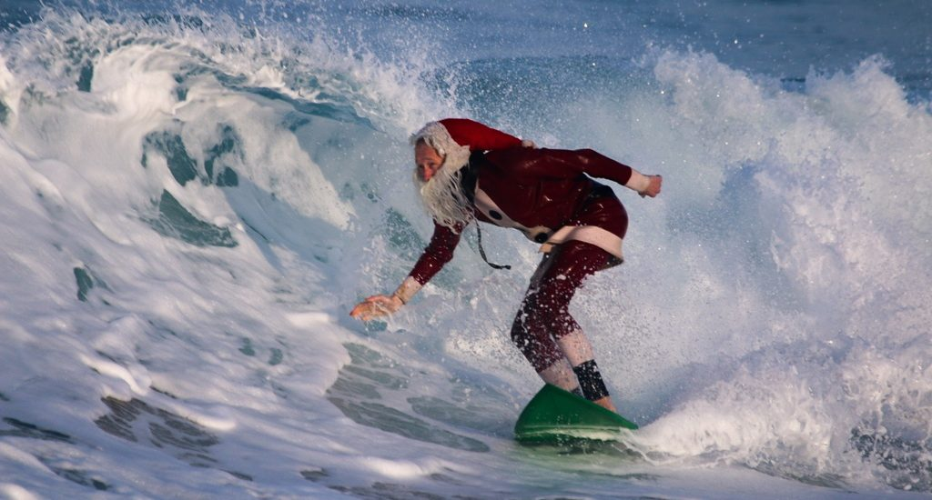 Surfing Santa makes an early holiday delivery to the South Bay