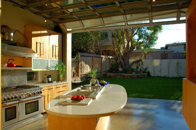 The kitchen opens to and extends the backyard.
