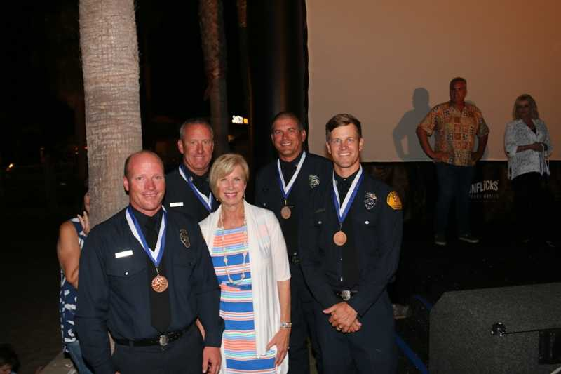 Rescue boat captains Rob Pelkey, Lance Dempsey and Matt Rhodes, and Ocean Lifeguard Specialist Brian Kari, winners of the Medal of Valor, with Hahn.